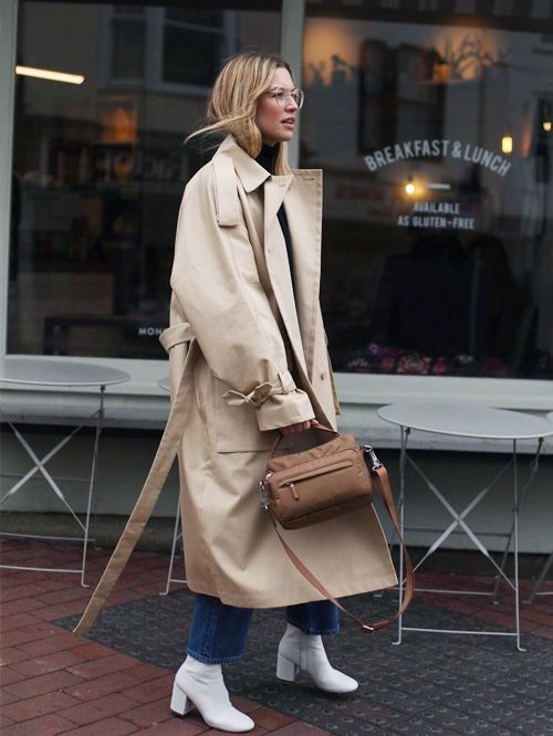 a stylish work look with a black turtleneck, blue jeans, white boots, a tan trench and a brown bag
