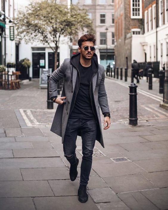 a black t-shirt, hoodie, black jeans, a grey coat and black boots is a stylish monochromatic look for the fall