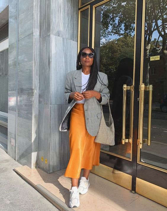 a stylish look with a white tee, a yellow slip midi, a grey plaid blazer, white trainers and a grey tote is chic