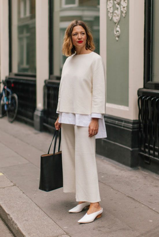 a chic outfit with a white shirt, a jumper, creamy trousers, white shoes, a black tote is ideal for work