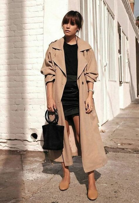 a stylish fall look with a black top, a black mini, a tan oversized trench, tan mules and a black bucket bag