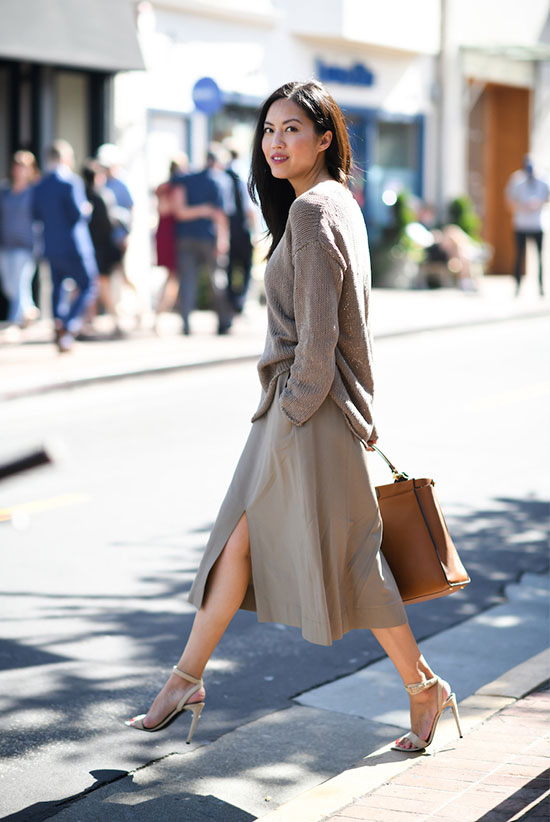 a lovely fall outfit with an oversized taupe jumper, a grey leather A-line midi, white heels and a brown tote