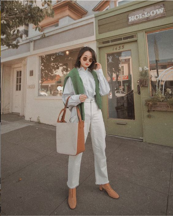 a fall outfit with a white shirt, white jeans, orange booties, a greye jumper and a two tone bag