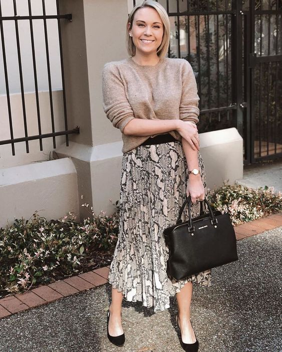 a simple work fall outfit wiht a taupe jumper, a snakeskin printed pleated midi, black heels and a black tote