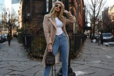 42 a white tee, blue jeans, a tan coat, a beret, white booties and a brown backpack for a stylish and simple look