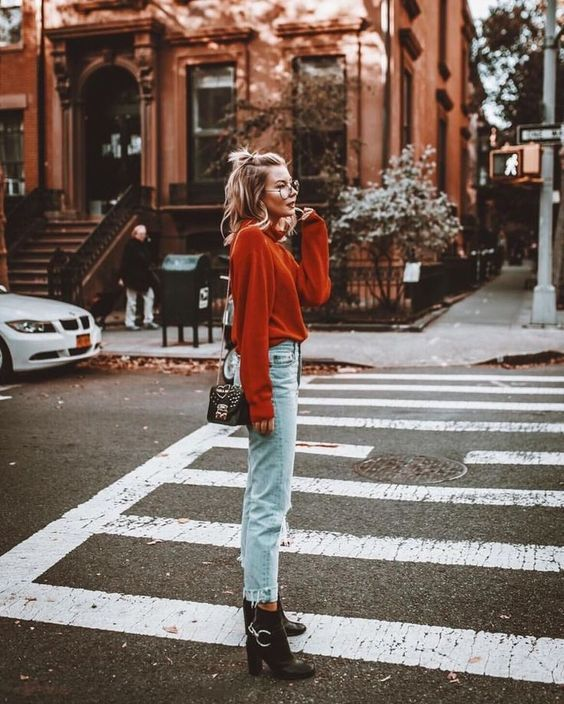 an elegant fall look with a rust-colored sweater, bleached jeans, black boots and a small black bag