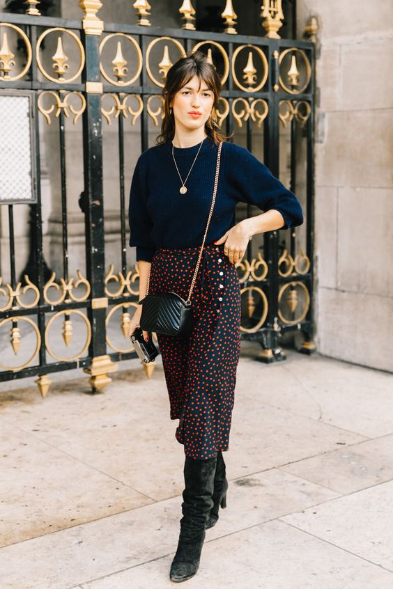 a stylish fall outfit with a navy jumper, a polka dot black and red midi, black boots and a black crossbody bag