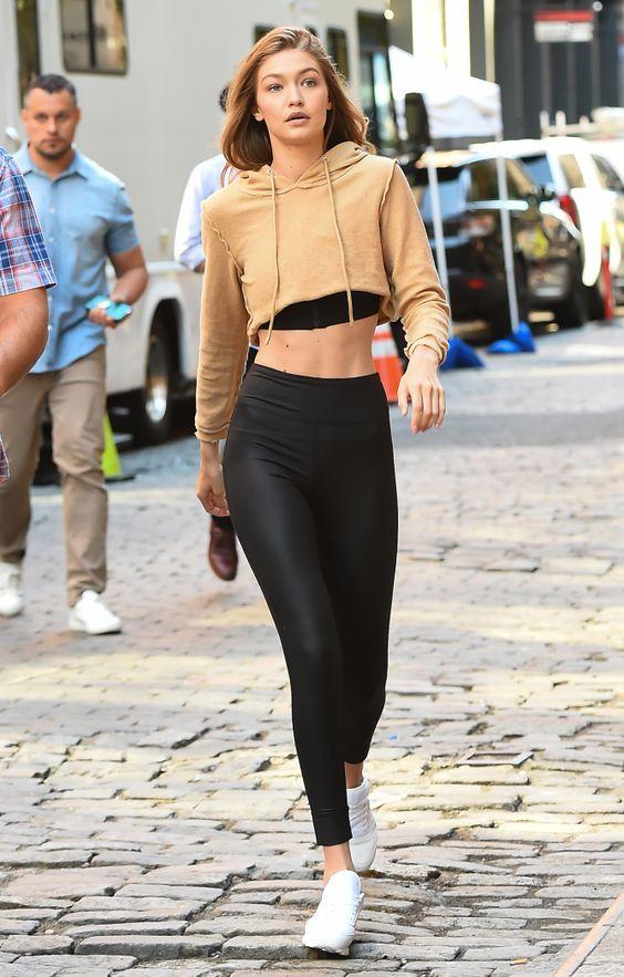 Gigi Hadid wearing black leggings, a black crop top, a tan hoodie, white sneakers