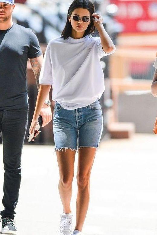 Kendall Jenner wearing an oversized white t-shirt, blue denim biker shorts, white sneakers looks fabulous