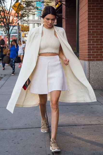 With beige crop top, white mini skirt and beige coat
