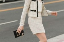 With beige lace top, black and golden clutch and black high heels