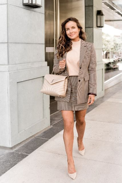 With beige shirt, beige leather bag and beige pumps