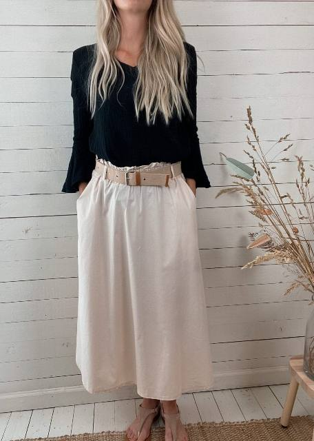 With black bell sleeved shirt and beige flat shoes