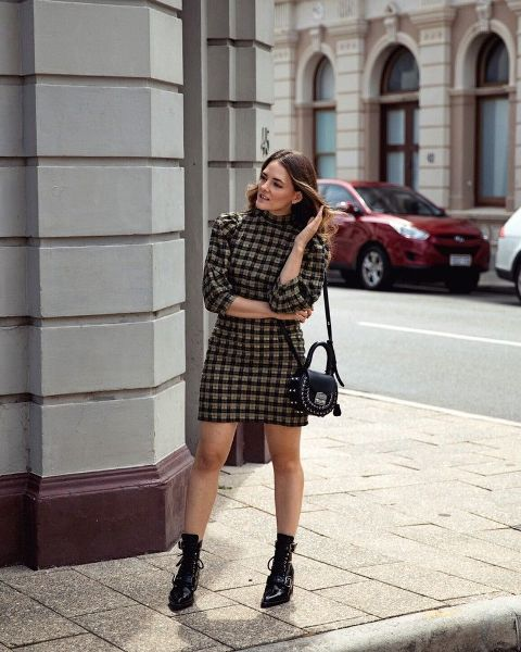 With black embellished bag and black lace up mid calf boots