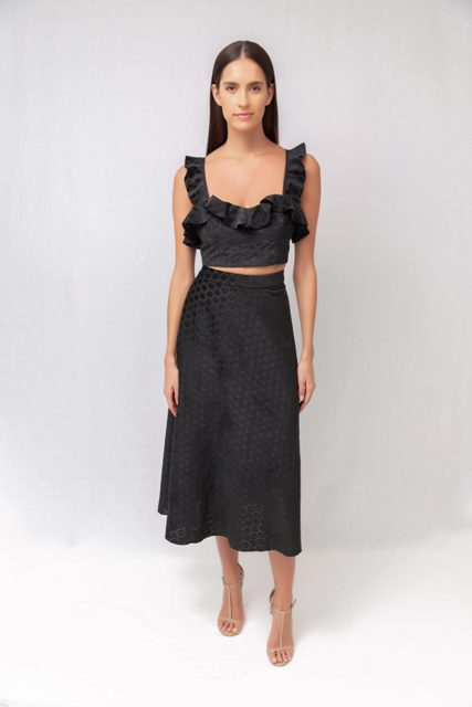With black midi skirt and beige sandals
