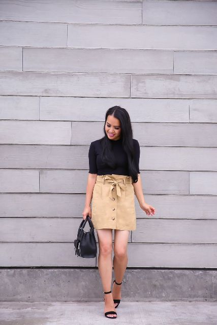 With black shirt, black leather bag and black ankle strap high heels