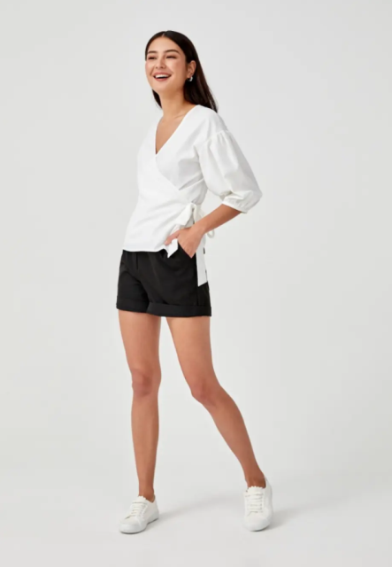 With black shorts and white flat shoes