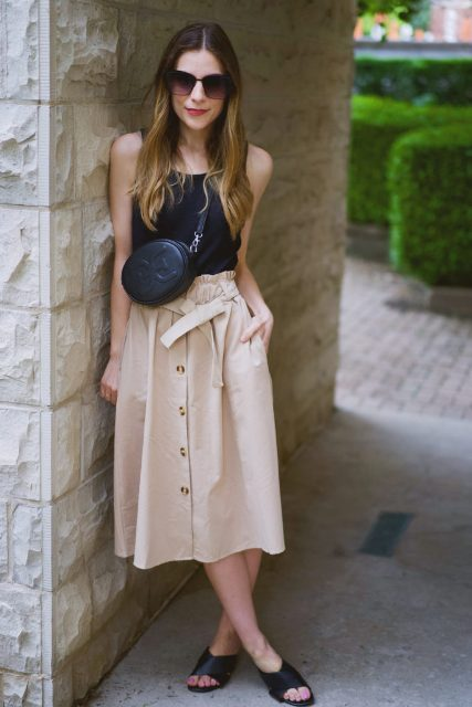With black sleeveless top, black crossbody bag and black mules