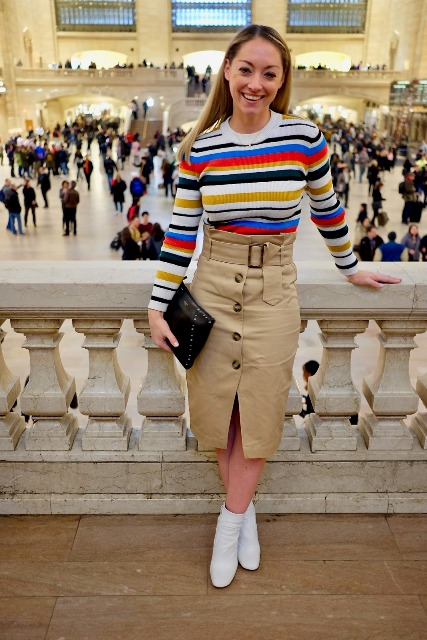 With colorful striped shirt, black clutch and white ankle boots