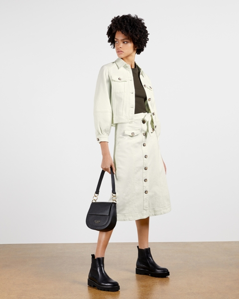 With dark gray shirt, white jacket, black leather bag and black flat ankle boots