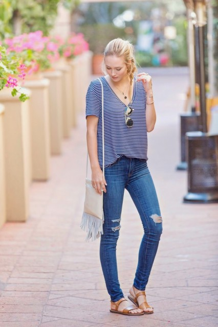 With distressed skinny jeans, fringe bag and brown leather flat sandals