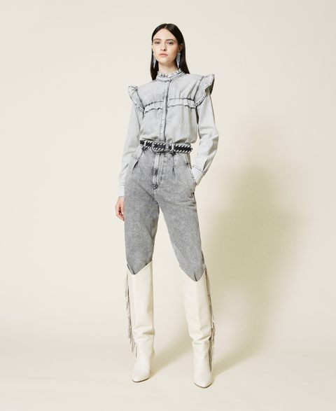 With gray loose jeans, embellished belt and white high boots