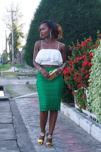With green lace skirt, golden clutch and golden sandals