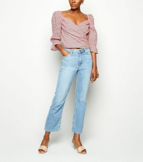 With light blue cropped jeans and beige mules
