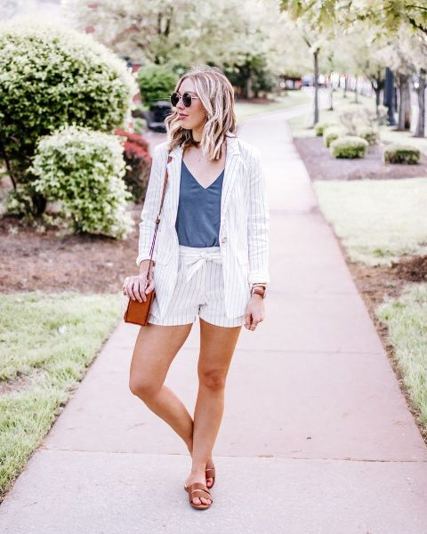With navy blue V-neck top, brown bag and brown flat sandals