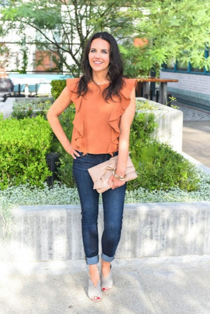 With navy blue cuffed jeans, pale pink clutch and gray mules