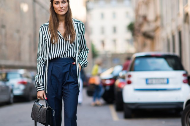 With navy blue high-waisted trousers and black leather bag