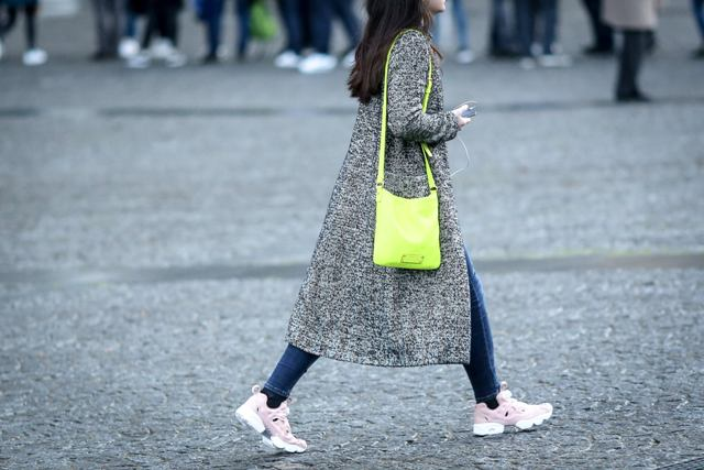 With navy blue jeans, printed coat and green bag
