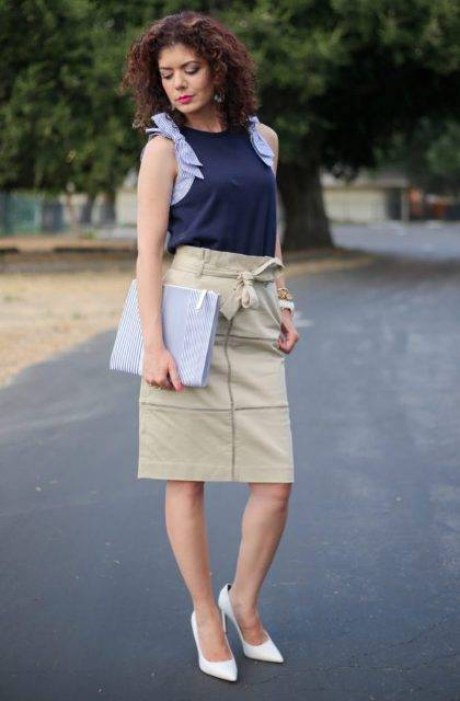 With navy blue sleeveless top, striped clutch and white pumps