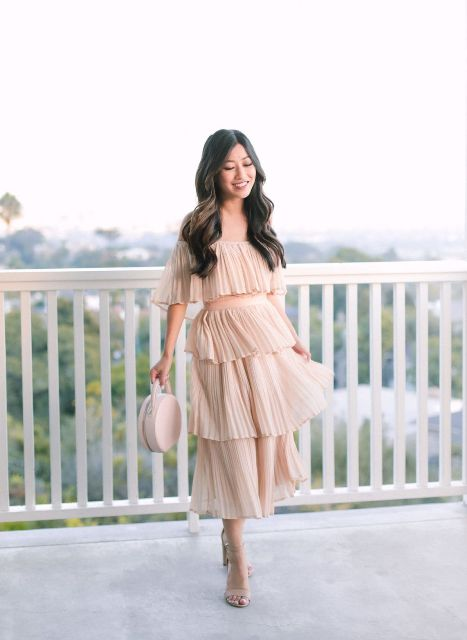 With pale pink rounded bag and beige sandals