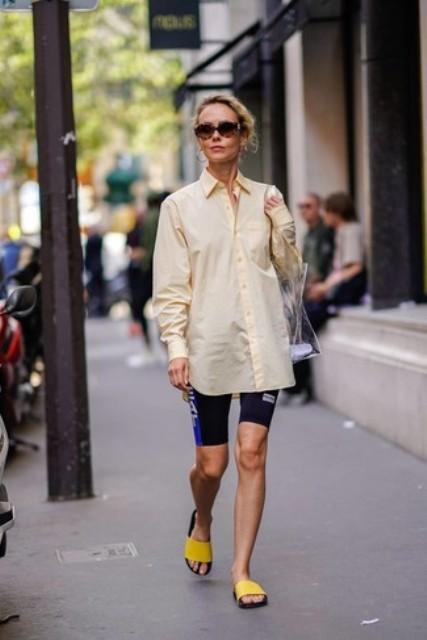 With sporty shorts, transparent bag and yellow flat sandals