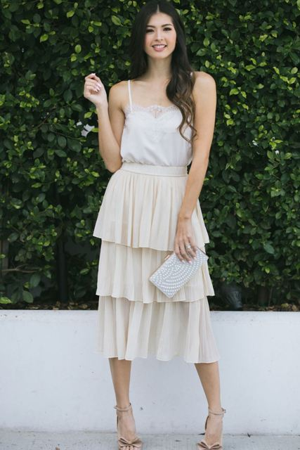 With white lace top, white embellished clutch and beige embellished sandals