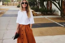 With white loose shirt, black clutch and black flat sandals