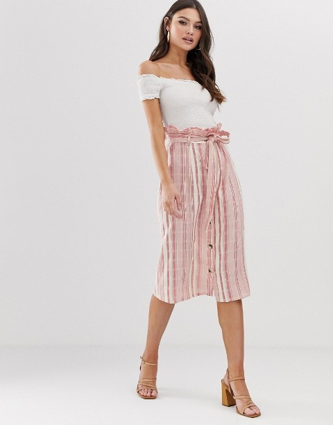 With white off the shoulder top and beige high heels