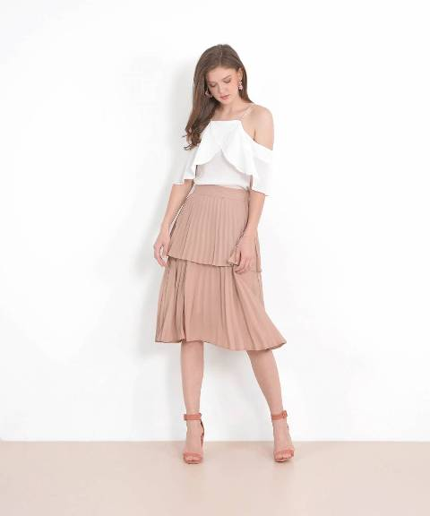 With white ruffled off the shoulder shirt and pale pink ankle strap shoes