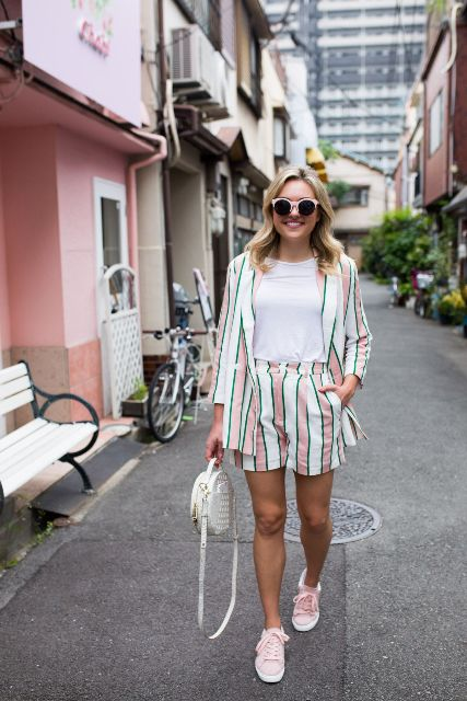 With white t shirt, white rounded bag and pale pink flat shoes