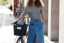 a Parisian chic outfit with a striped tee, a blue A-line denim button up midi, black moccasins and a black backpack
