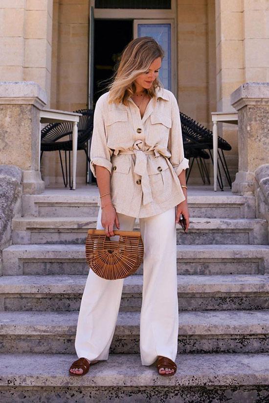 a beige utility shirt, white wide leg pants, brown slide sandals, a brown bamboo clutch