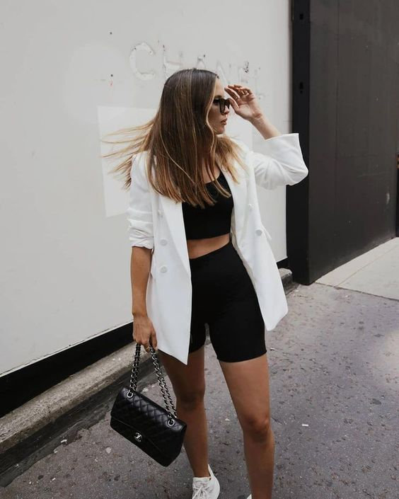 a black and white look with a crop top, black biker shorts, white sneakers, an oversized white blazer, a black bag