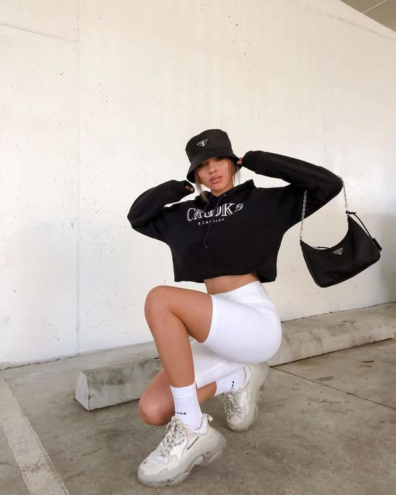 a black cropped hoodie, white biker shorts, a black bag and a bucket hat plus neutral trainers