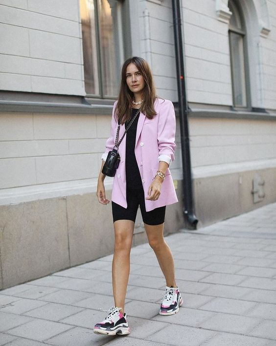a black t-shirt, black biker shorts, a pink oversized blazer, pink and black trainers and a black crossbody bag