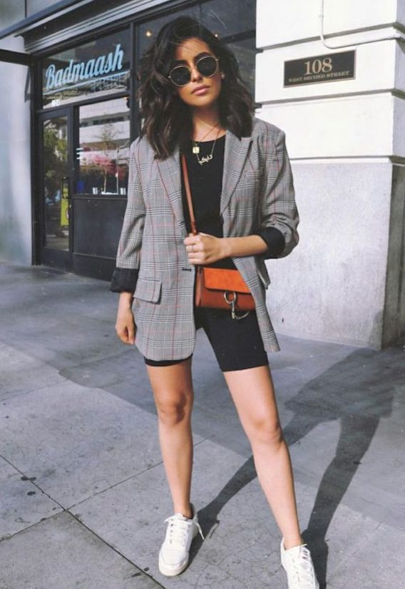 a black tee, black biker shorts, white sneakers, a grey plaid blazer, an amber crossbody bag and layered necklaces