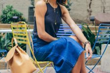 a black top, a blue denim midi skirt, brown heels, an amber backpack for a relaxed and feminine look