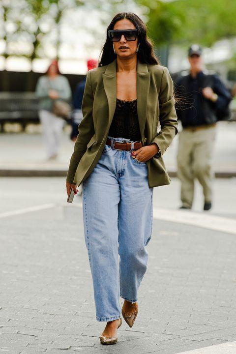 a black top, light blue barrel jeans, snake skin print pumpkins, a green blazer and a brown belt