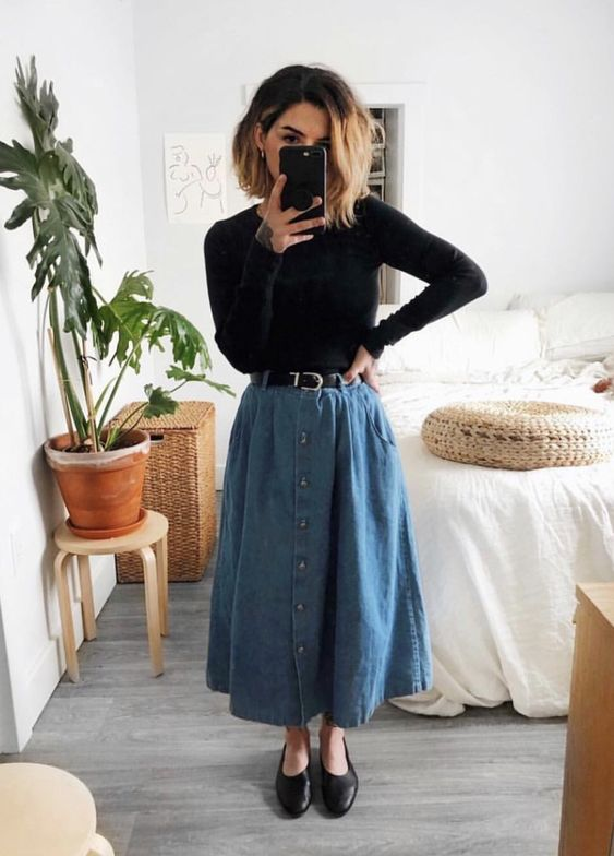 a black turtleneck, a blue denim midi A-line skirt, black flat shoes and a black belt for a retro-inspired look
