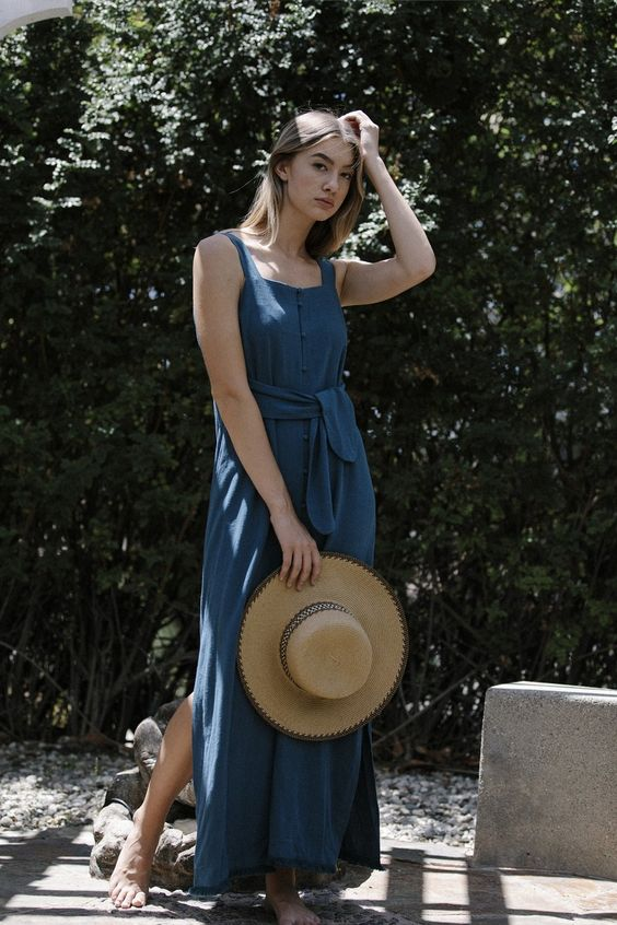 a blue linen maxi sundress on buttons, with thick straps, a square neckline, a sash and a straw hat for a vacation